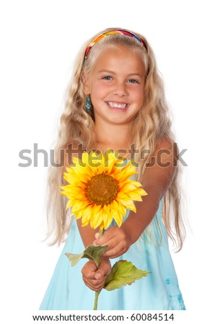 a beautiful little girl smiling and holding a sunflower - stock photo