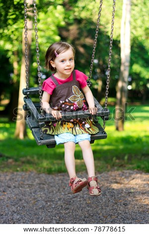 A beautiful little girl swinging at the playground in the park - stock photo
