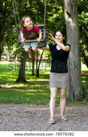 A beautiful little girl swinging with her pretty mother at the playground in the park - stock photo