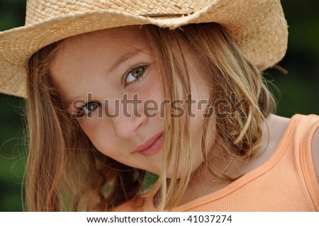 a beautiful little girl wears a cowboy hat - stock photo
