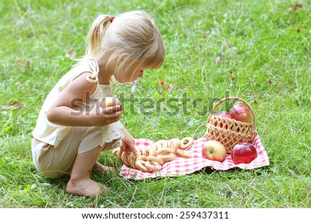 a beautiful little girl with apples on the nature - stock photo