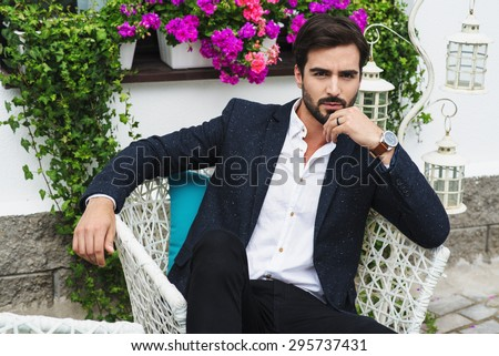 A beautiful man in a jacket and shirt sitting on a chair and looking at the camera, green and flowers, outside