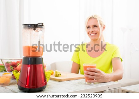 A beautiful mature woman enjoying a smoothie or juice with fruits in the kitchen.  - stock photo