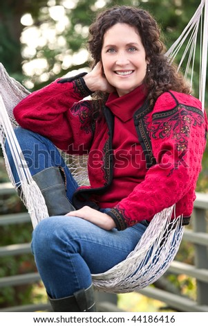 A beautiful mature woman sitting on a hammock