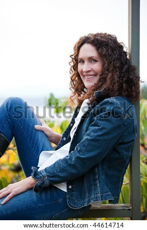 A beautiful mature woman sitting outdoor - stock photo