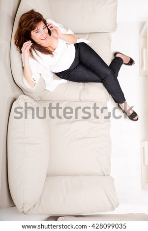 A beautiful mature woman talking on her cell phone on the sofa - stock photo