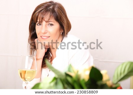 A beautiful mature woman with a glass of white wine. - stock photo