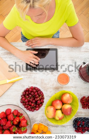 A beautiful mature woman with a smoothie in the kitchen using a tablet.