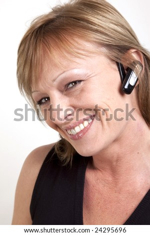A beautiful mature woman with a wireless earpiece and head tilted to side - stock photo