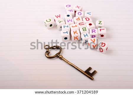 A beautiful metal key and cube letters of alphabet side by side on a sheet of paper - stock photo