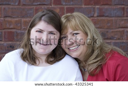A beautiful middle aged mother with her special needs daughter, closeup with selective focus