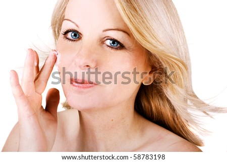 A beautiful middle aged woman applying cream to her face.