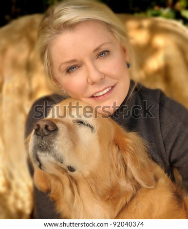 A beautiful middle aged woman In Love with Her Golden retriever - stock photo