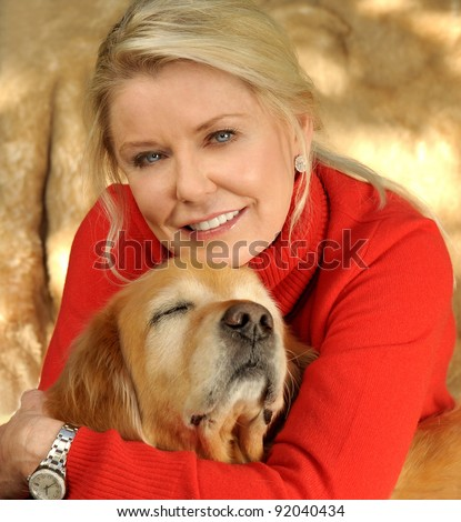 A beautiful Middle aged Woman who Loves her Golden Retriever - stock photo