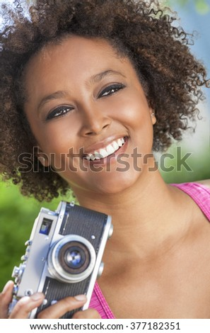 A beautiful mixed race African American girl or young woman looking happy taking pictures or photographs with a retro digital camera - stock photo