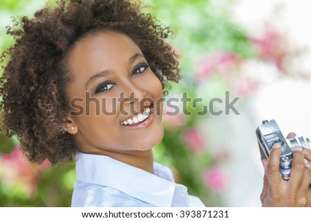 A beautiful mixed race African American girl or young woman looking happy taking pictures or photographs outside with a retro digital camera - stock photo