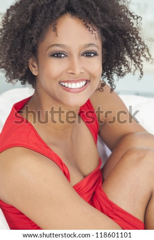 A beautiful mixed race African American girl or young woman lwearing a red dress looking happy and smiling