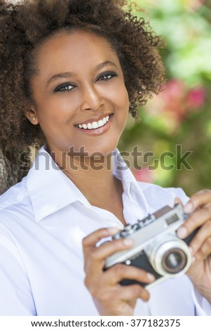 A beautiful mixed race African American girl or young woman outside looking happy taking pictures or photographs with a retro digital camera - stock photo