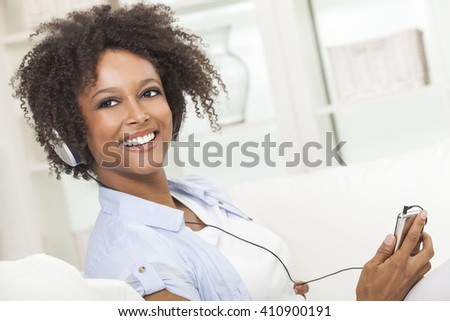 A beautiful mixed race African American girl or young woman relaxing at home listening to music on mp3 player and headphones - stock photo