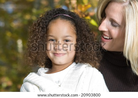 A beautiful mixed race mother and her daughter - stock photo