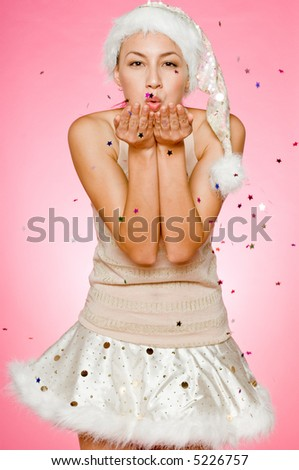 A beautiful mixed race woman blowing kisses on pink background - stock photo