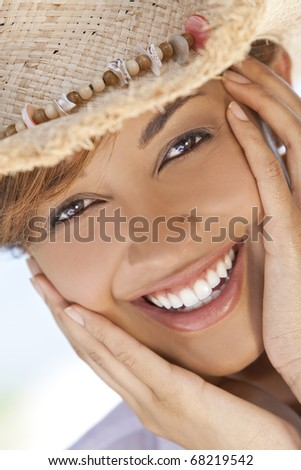 A beautiful mixed race young woman laughing and having fun wearing a straw cowboy hat, shot under a palm tree on a tropical beach - stock photo