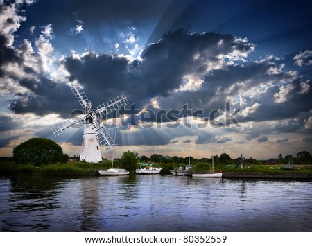 a beautiful moody image of a traditional norfolk windmill or wind pump with four moored sailing boats at early evening with a spectacular sun beam sky beyond - stock photo