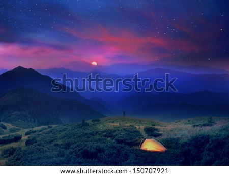 A beautiful moonrise in the foothills of the Alps affect the viewer's imagination, dense virgin forests on the slopes contribute to conceal the traces of civilization - stock photo