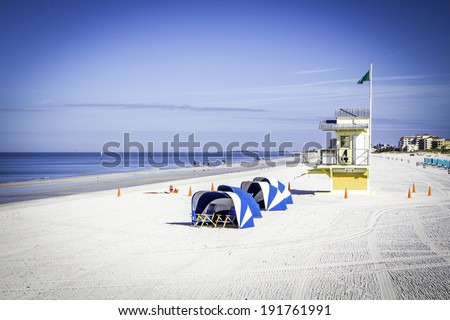 A beautiful morning on Clearwater Beach.  The sky is blue and the sand is freshly raked. - stock photo
