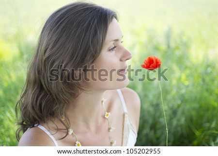 A beautiful, natural young woman with a poppy and a daisy chain - stock photo