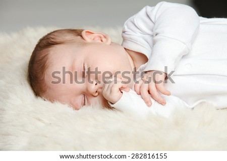 A beautiful newborn baby , dressed in white