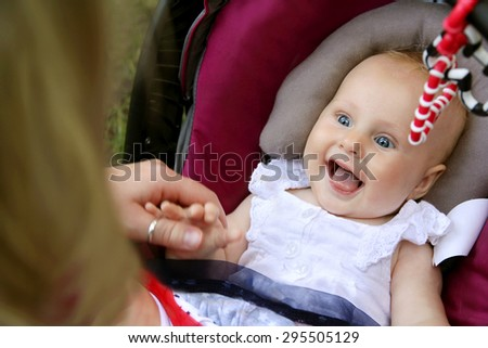 A beautiful newborn baby girl is laughing and sticking out her tongue as her mother holds her hands while she sits in her car seat. - stock photo