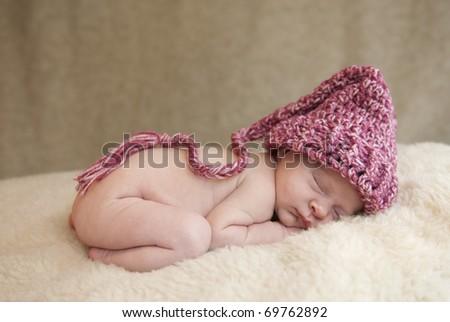 A beautiful newborn baby girl wearing a hat, soft focus - stock photo