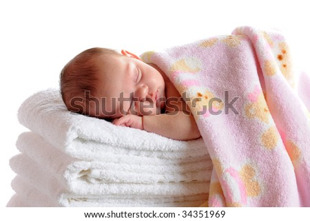 A beautiful newborn sleeping on a stack of white towels and covered with a soft pink blanket.  Isolated on white. - stock photo