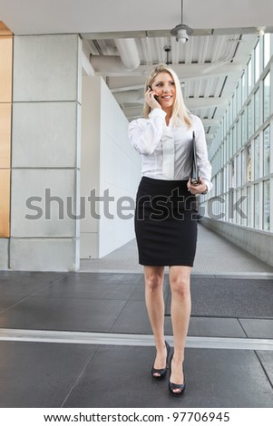 A beautiful office lady talking on the phone and walking - stock photo