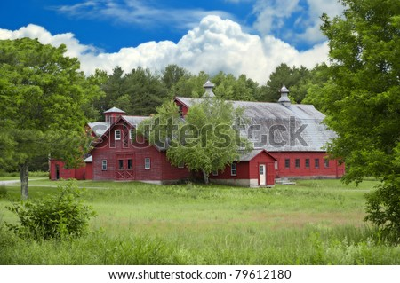 A beautiful old bright red barn sits among the trees in the countryside in Vermont, USA. - stock photo