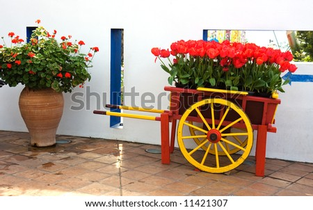 A beautiful old hand cart with tulips on a terrace