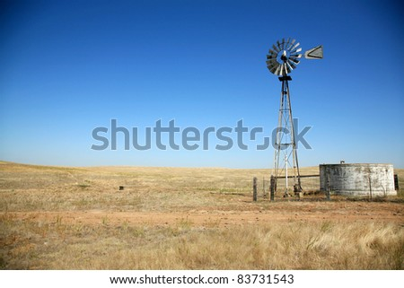 a beautiful old windmill water tower in a field on a beautiful summer day with a cloudless blue sky in a field - stock photo