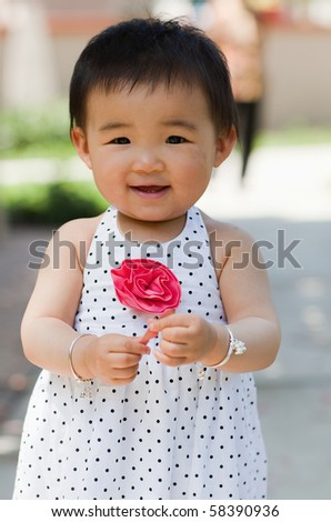 a beautiful one-year-old girl in dotted dressdress with her grandma standing behind her