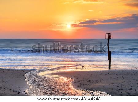 A beautiful orange sunrise over a beach in Dorset, UK - stock photo