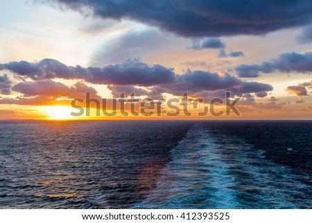 A beautiful orange sunset at sea in wake of ship - stock photo