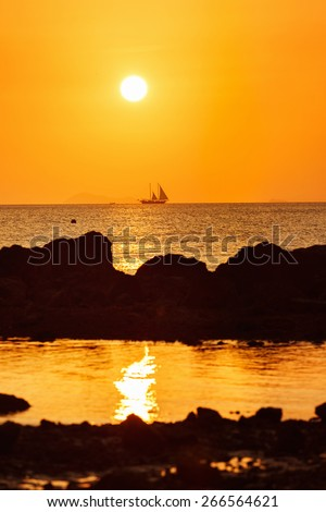 A beautiful orange sunset seascape with a sailing boat at the background. - stock photo