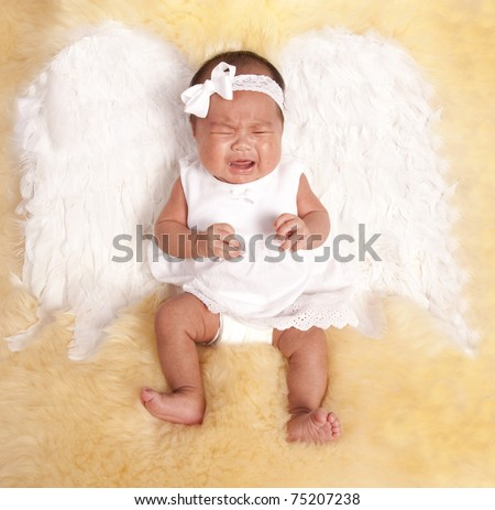 a beautiful oriental baby laying on a fur rug with her white angel wings on her back, with a sad expression on her face. - stock photo