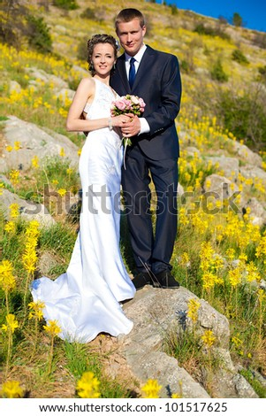 A beautiful pair of bride and groom enjoy a moment of happiness. Posing on their wedding day in the spring.
