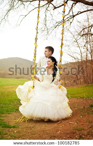 A beautiful pair of bride and groom enjoy a moment of happiness, riding on a swing. Wedding day in spring. - stock photo