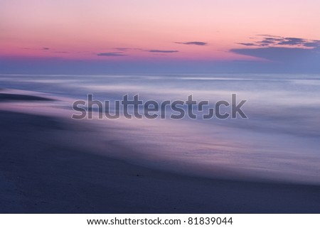 A beautiful pastel colored sunset on a quiet, secluded beach. - stock photo