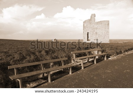 a beautiful path with benches to view Ballybunion beach and castle in sepia - stock photo