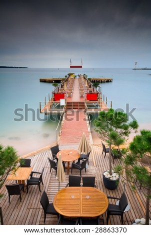 A beautiful pier going into silky and smooth tropical waters - stock photo