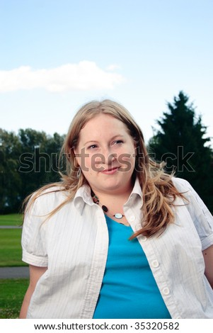 A beautiful plus size woman sitting in a park