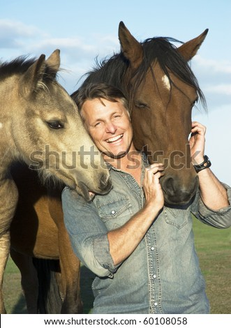 A beautiful portrait of a happy laughing man bonding with his two horses - stock photo